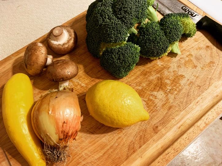 fresh ingredients like broccoli, mushrooms, yellow squash, onions, and lemons.