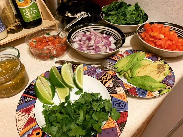 fresh veggie toppings for double deck vegan cauliflower tacos. Tomatoes, red onions, avocado, spinach, cilantro, limes, salsa