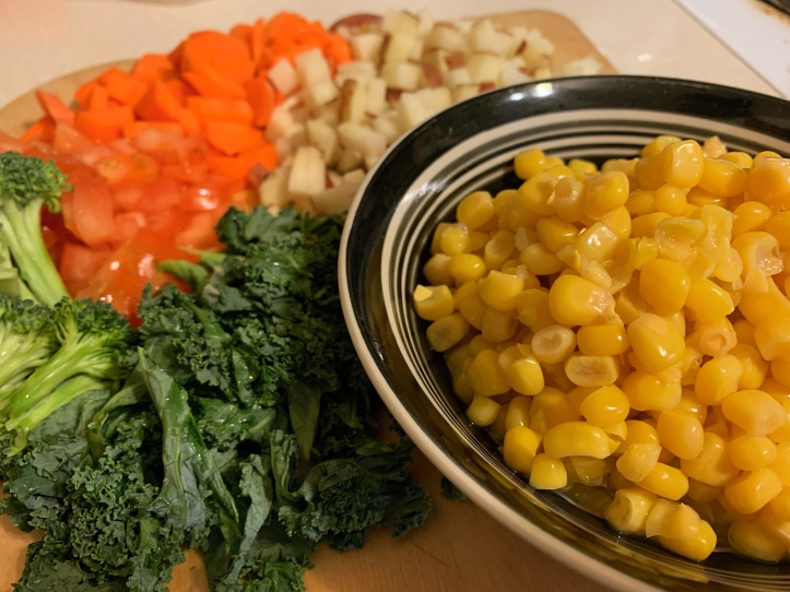 Vegan Corn Chowder ingredients: corn, kale, tomatoes, potatoes, and carrots