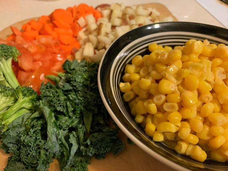 Vegan Corn Chowder ingredients: corn, kale, tomatoes, potatoes, and carrots