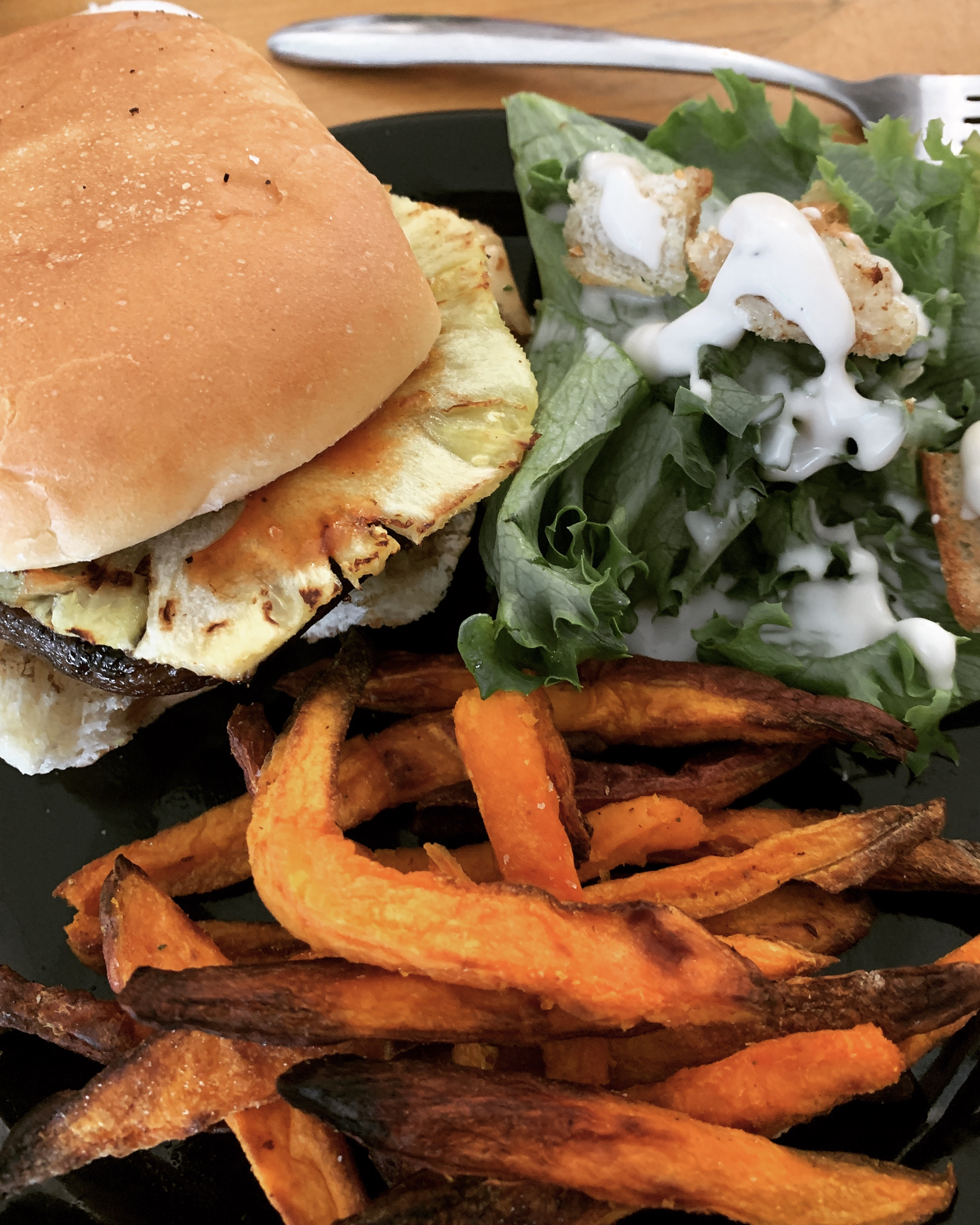 Vegan Mushroom Burger with sweet potato fries and vegan caesar salads